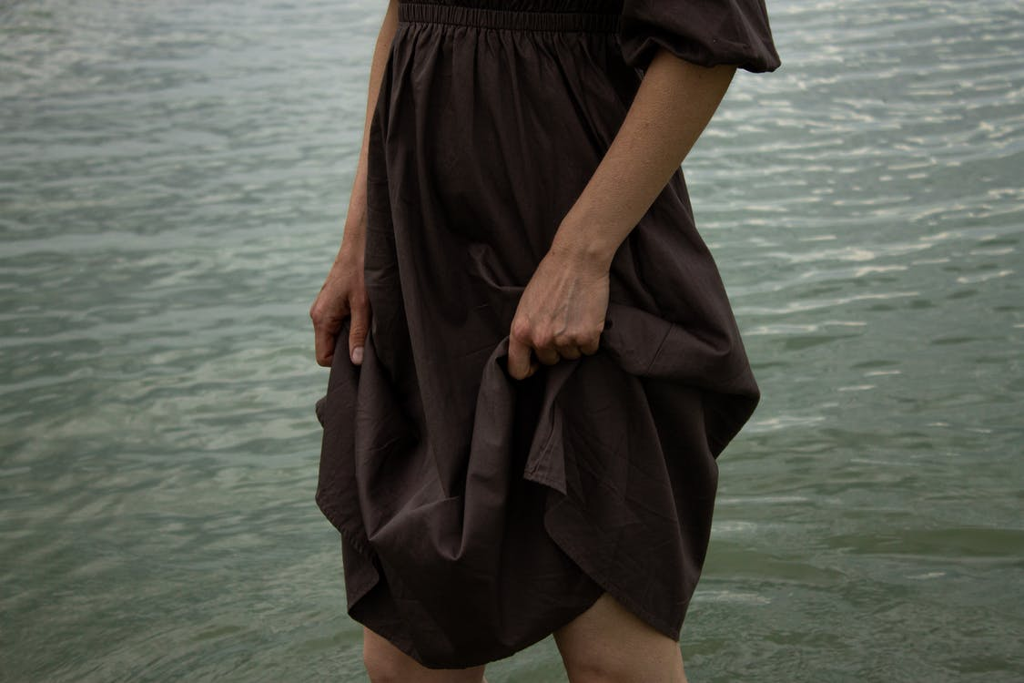 Crop anonymous female holding long dress while standing in river and enjoying freedom in nature