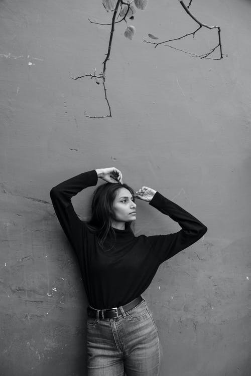 Woman in Black Long Sleeve Shirt Leaning on Wall
