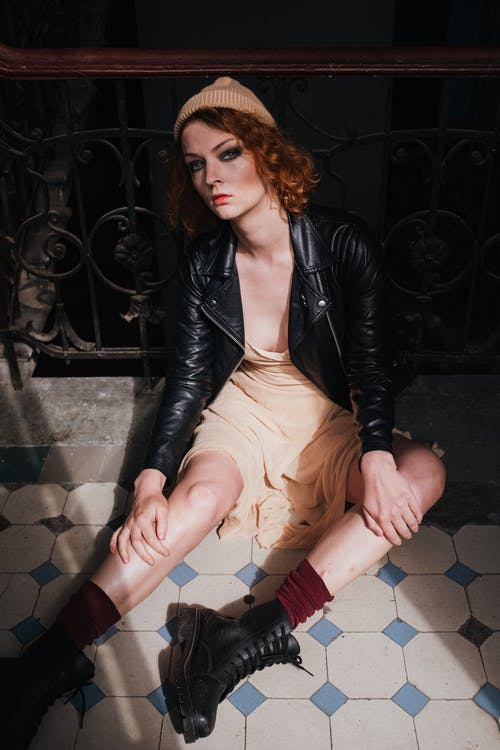 Woman in Black Leather Jacket and Beige Skirt Sitting on Floor