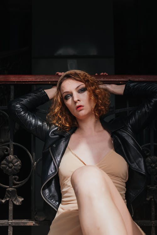 Woman in Black Leather Jacket Sitting on Black Leather Chair