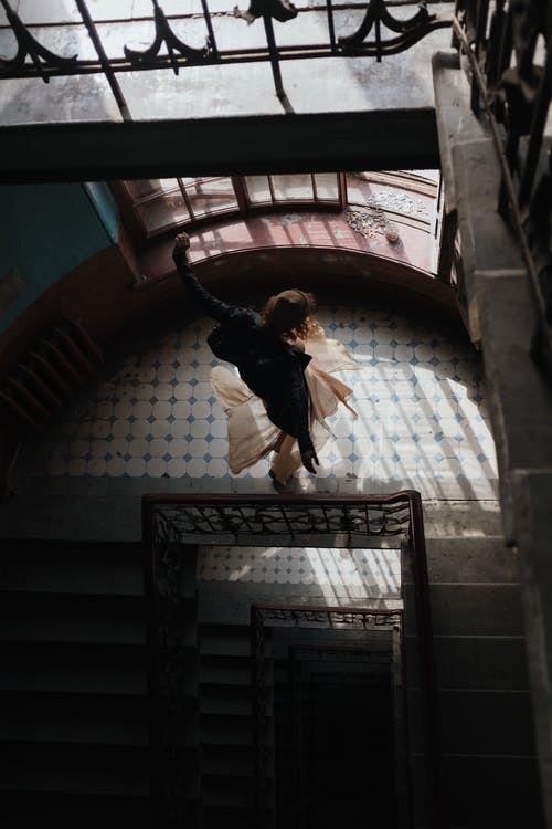 Man in Black Jacket and Brown Pants Jumping on Brown Concrete Stairs