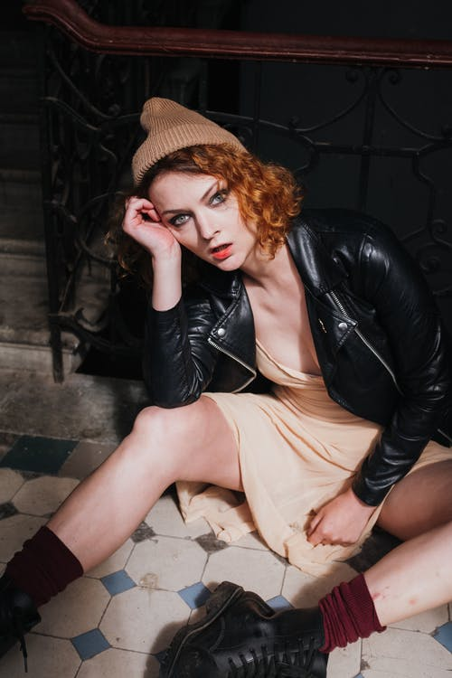 Woman in Black Leather Jacket and Brown Skirt Sitting on Black Floor