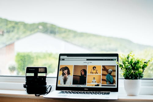 Black instant photo camera with laptop and decorative potted plant standing on white windowsill