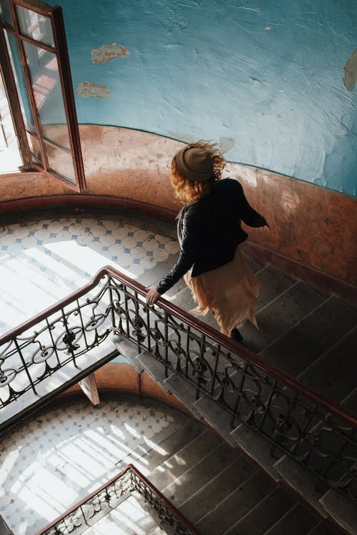 Woman in Black Long Sleeve Shirt and Black Pants Standing on Brown Staircase