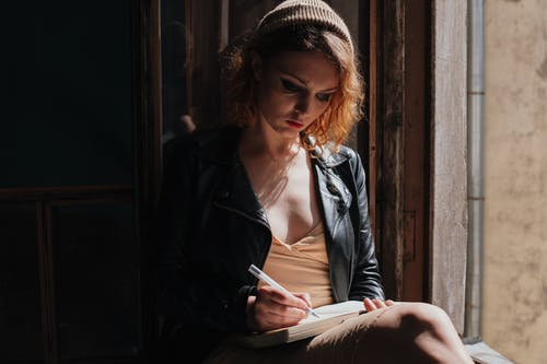 Woman in Black Leather Jacket and Knit Cap Reading Book