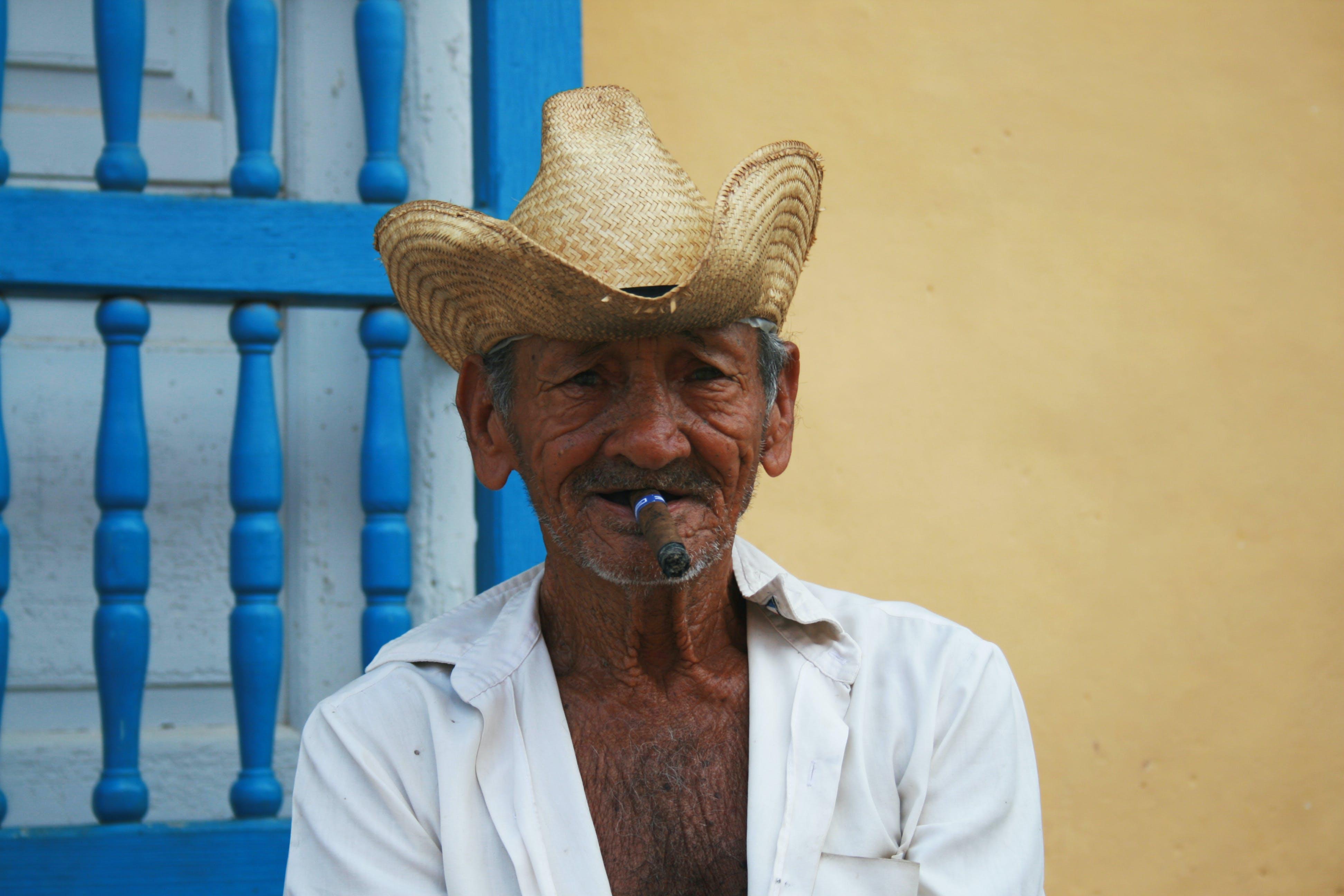Man Wearing Straw Hat While Smoking