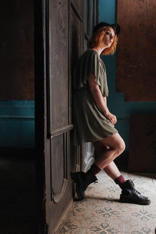 Woman in Gray Long Sleeve Shirt and Brown Skirt Standing Beside Blue Wooden Door