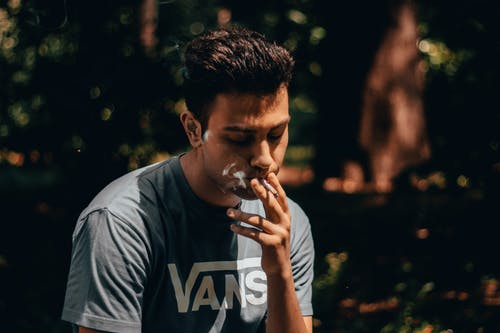Man in Gray Crew Neck T-shirt Smoking Cigarette