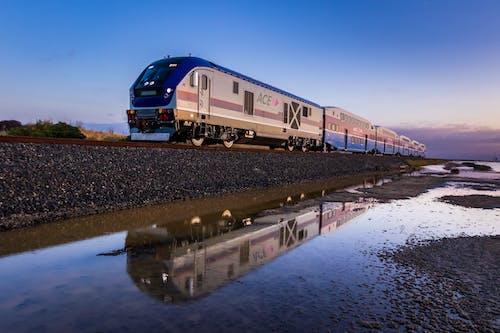 Blue and White Train on Rail Tracks