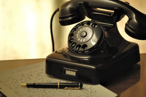 Black Rotary Telephone Beside Ball Pen on White Printed Paper