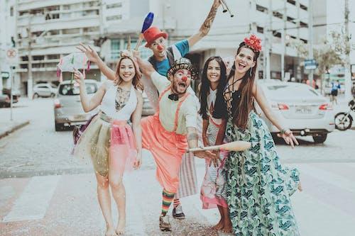 Happy clowns near stylish girlfriends on city street