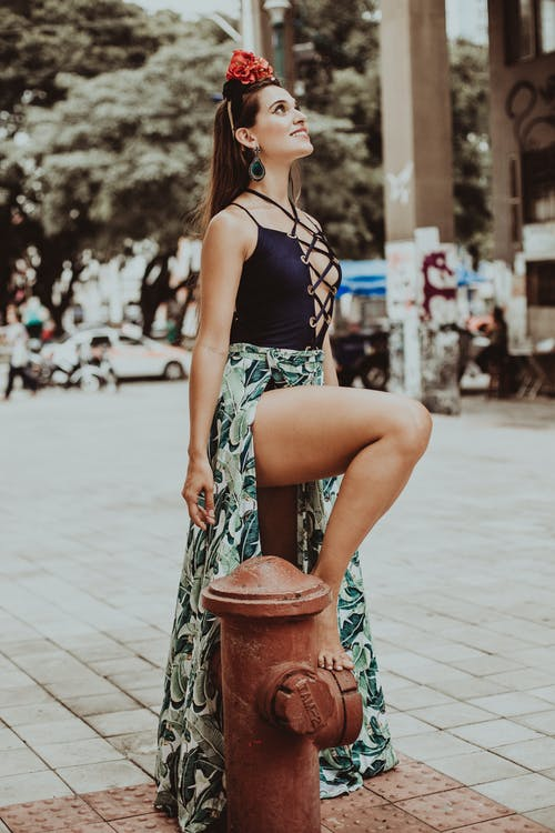 Trendy smiling woman in modern apparel on street pavement