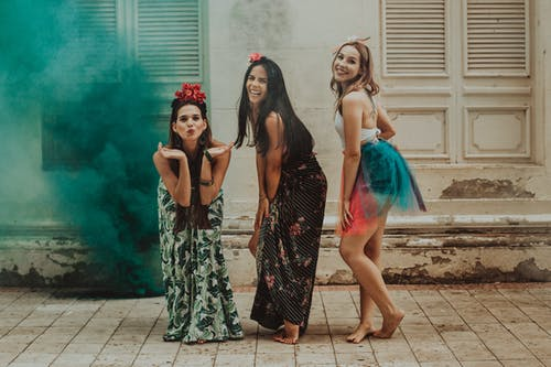 Young happy barefoot girlfriends in stylish apparel and adornments on heads laughing on pavement near cloud of artificial smoke while looking at camera