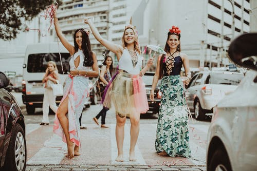 Young cheerful barefoot women in stylish apparel with raised arms standing on street pavement while looking at camera