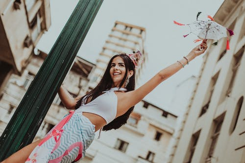 Happy model in stylish apparel with decorative umbrella on street
