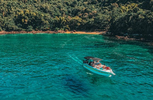 Boat with tourists floating on azure transparent seawater