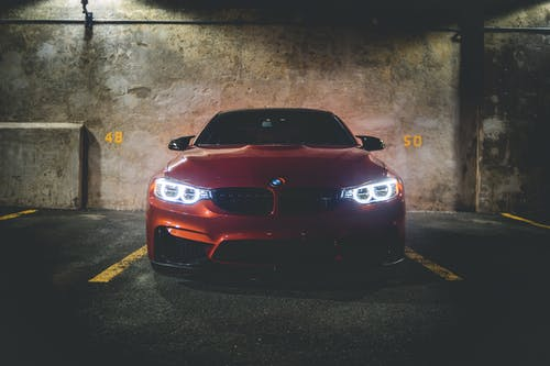 Red car in garage under flashlight