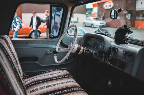 Vintage cabin of retro car with dashboard behind steering wheel and car seat on modern city