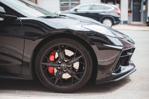 Luxury car with black wheels with metal brake discs and glossy headlight on roadside