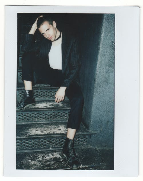 Woman in Black Blazer and Black Pants Sitting on Stairs