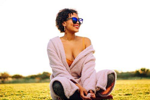 Low angle of cheerful young ethnic female with curly hair in bathrobe and sunglasses smiling while sitting on grassy lawn with crossed legs and looking away