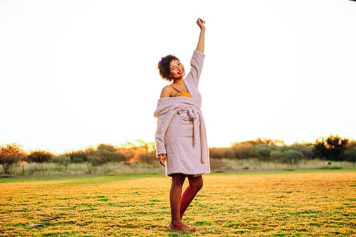 Side view of happy young African American lady with raised arm in comfy bathrobe smiling while enjoying sunny day on grassy meadow