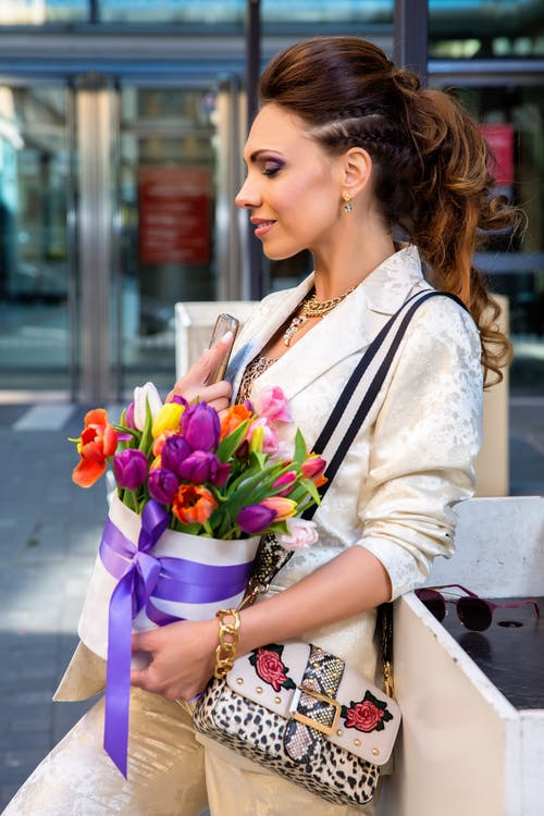 Woman in White Long Sleeve Shirt Holding Bouquet of Flowers