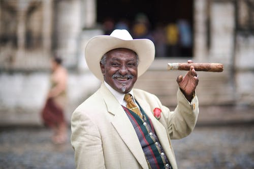 Man in White Suit Holding Brown Wooden Stick