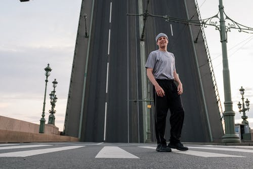 Man in White Crew Neck T-shirt and Black Pants Standing Near Gray Building