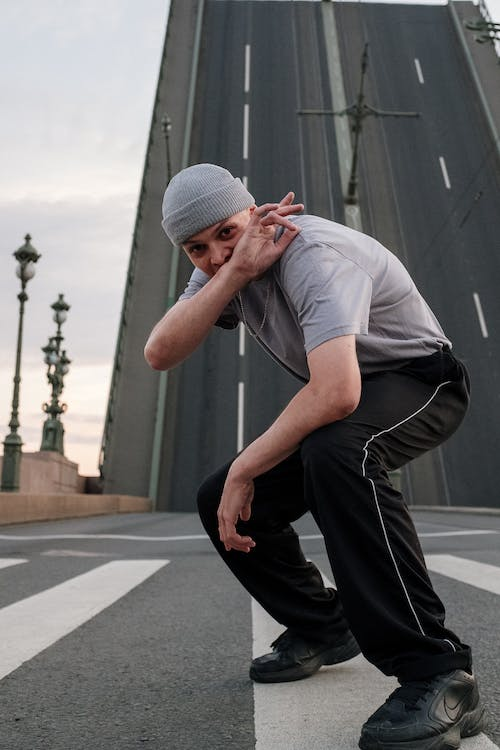 Man in Gray Crew Neck T-shirt and Black Pants Sitting on Gray Concrete Wall during