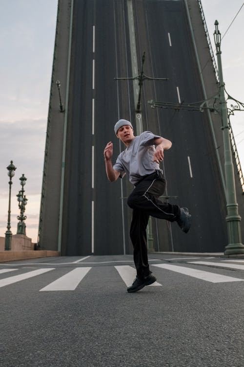 Man in Black Pants and White Shirt Jumping on Gray Asphalt Road