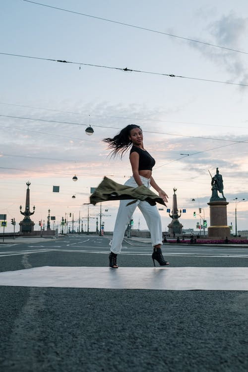 Woman in White Tank Top and Black Pants Standing on Gray Concrete Road