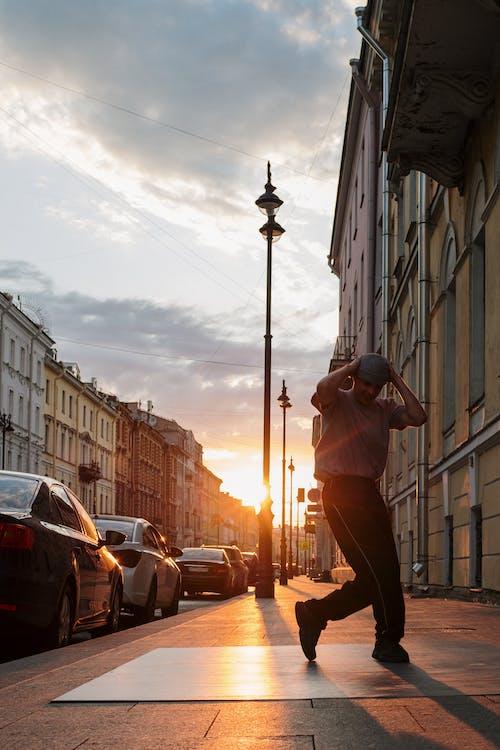 Man in Brown Pants and Black Hat Standing on Street