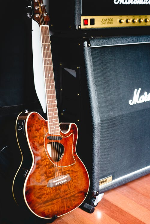 Brown Acoustic Guitar on Black and White Marshall Guitar Amplifier