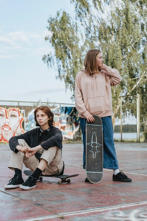Woman in Pink Long Sleeve Shirt and Blue Denim Jeans Sitting on Black and White Skateboard