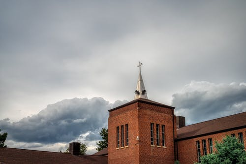 Old brick building against cloudy sky