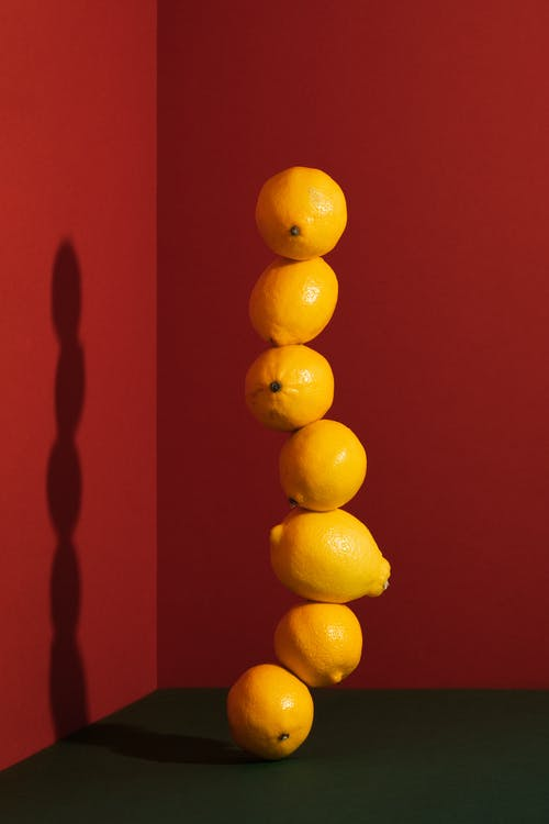 Yellow Citrus Fruits on Red Surface
