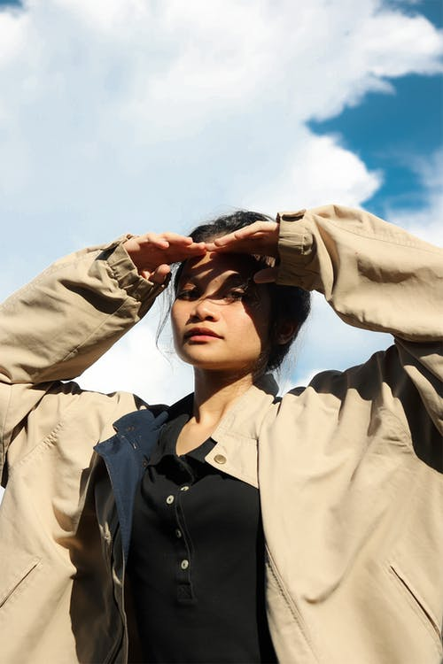 Woman in Beige Coat Covering Her Face With Her Hand