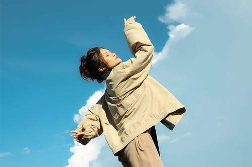 Man in Beige Dress Shirt and Black Pants Standing Under Blue Sky