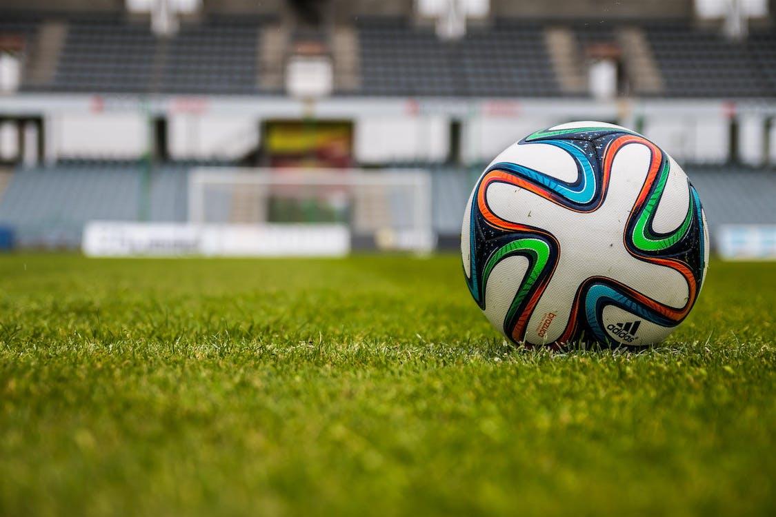 Blue Orange Black Green White Adidas Soccer Ball on Green Field