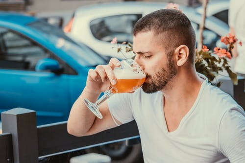 Man in White Crew Neck Shirt Drinking Orange Liquid from Clear Drinking Glass