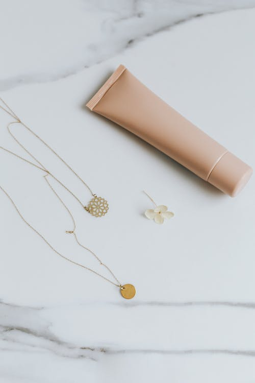 Gold Necklaces with Pendants Near Brown Tube