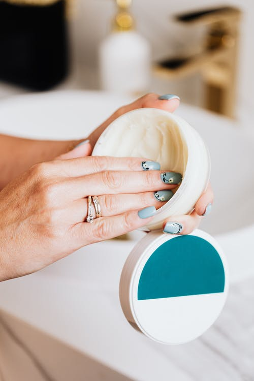 Fingers on Round White Container with White Cream