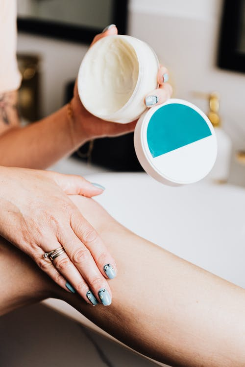Woman Hand Applying a Cream on the Skin of Her Leg