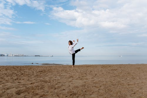 Woman in White Long Sleeve Shirt and Black Pants Standing on Brown Sand