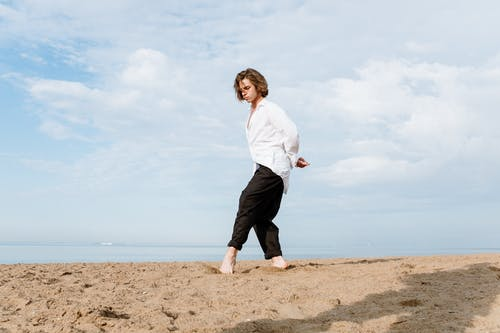 Man in White Dress Shirt and Black Pants Standing on Brown Sand