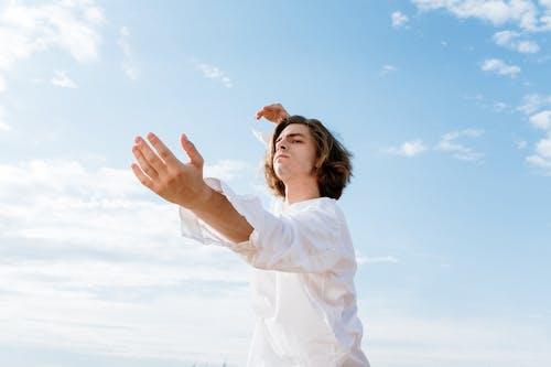 Woman in White Long Sleeve Shirt Raising Her Hands Under Blue Sky