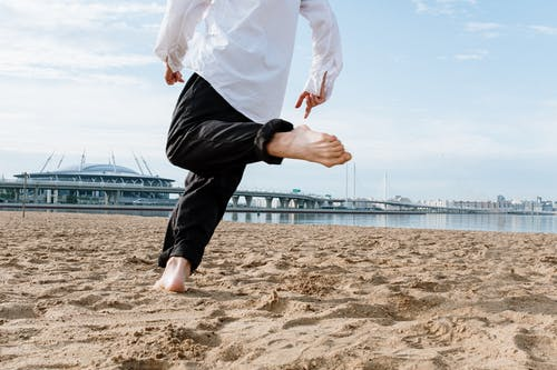 Man in White Dress Shirt and Black Pants Jumping on Brown Sand