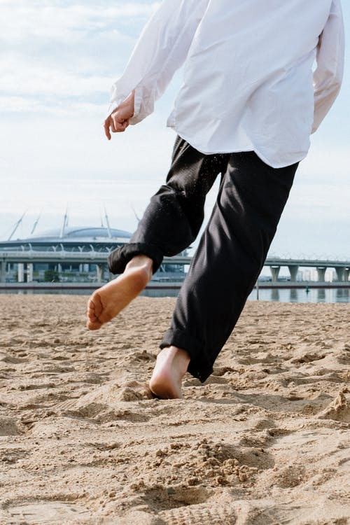 Man in White Shirt and Black Pants Jumping on Brown Sand