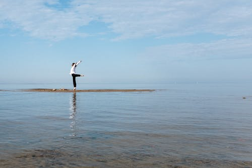 Person in Black Long Sleeve Shirt and Black Pants Standing on Sea Shore